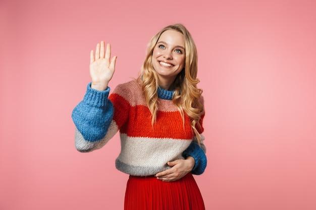 ピンクの壁を振って孤立してポーズをとって幸せな若いかなり美しい女性