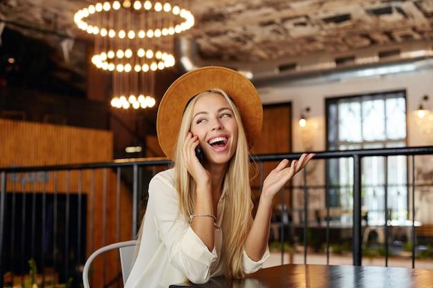Счастливая молодая симпатичная блондинка разговаривает по телефону, сидя в ресторане, весело улыбаясь и поднимая ладонь вверх, в белой рубашке и коричневой шляпе