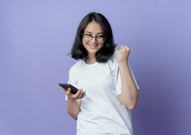 Счастливая молодая симпатичная кавказская девушка в очках смотрит в сторону, держащую мобильный телефон и сжимая кулак, изолированную на фиолетовом фоне с копией пространства