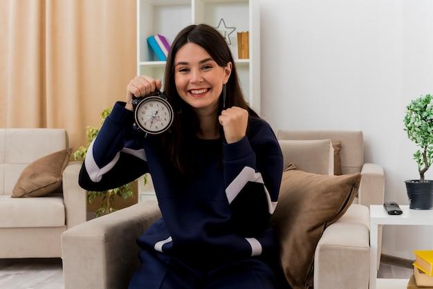 Felice giovane donna abbastanza caucasica seduto sulla poltrona nel soggiorno progettato tenendo la sveglia cercando e facendo sì gesto