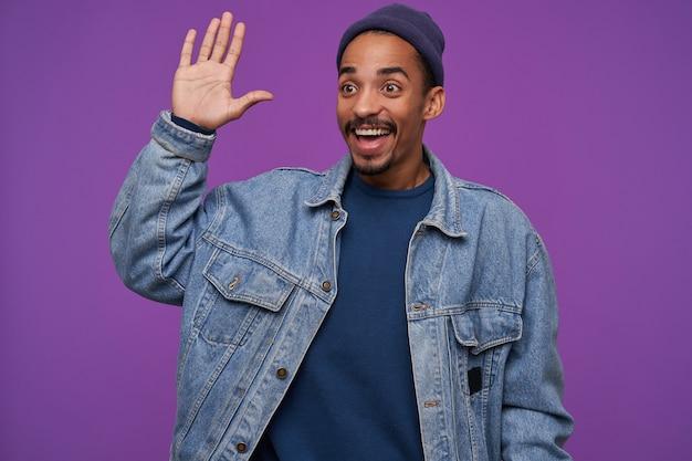 幸せな若いかなり暗い肌のひげを生やしたブルネットの男性は、友人に会い、こんにちはジェスチャーで手のひらを上げている間、紫色の壁の上でポーズをとっている間幸せに笑っている