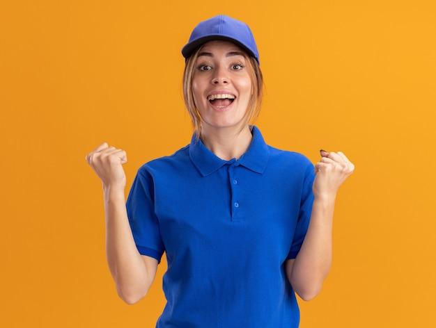 Счастливая молодая симпатичная доставщица в униформе держит кулаки на оранжевом