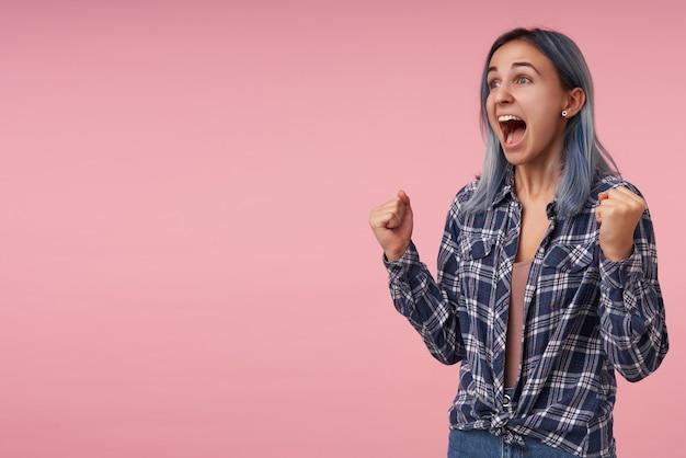何かを喜んで、ピンクでポーズをとって、大きな口を開けて叫びながら、彼女の拳を上げる自然なメイクで幸せな若いきれいな女性