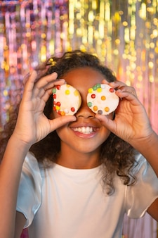 カップケーキを保持しているお祝いパーティーで幸せな若いかわいい女の子
