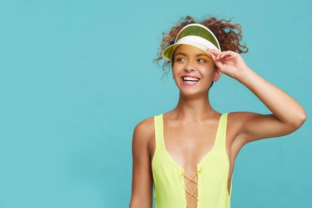 彼女のバイザーに手を上げて、青い背景の上に立っている間喜んで笑って水泳ウェアに身を包んだ幸せな若いかなり赤い髪の巻き毛の女性