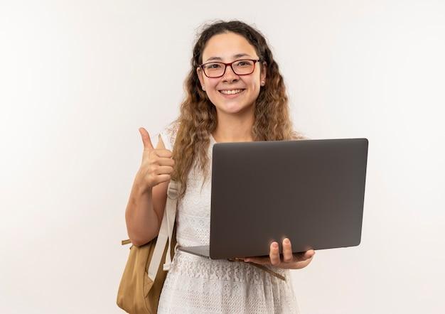 Счастливая молодая симпатичная школьница в очках и задней сумке, держащая ноутбук, показывает палец вверх изолированной с копией пространства