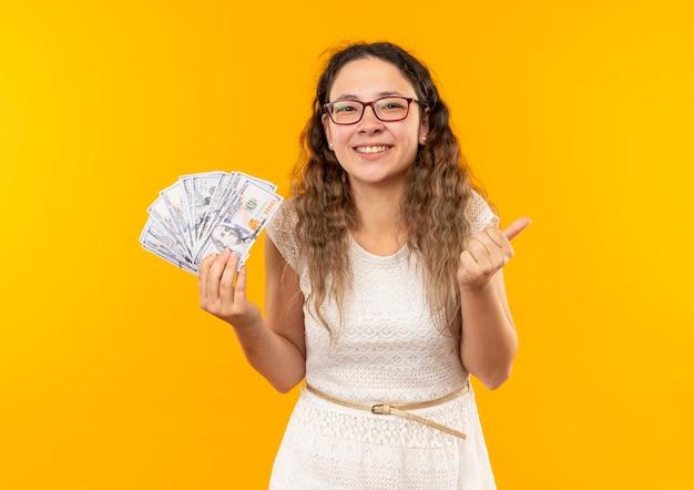 Счастливая молодая симпатичная школьница в очках, держащая деньги, показывает большой палец вверх изолированной на желтом с копией пространства