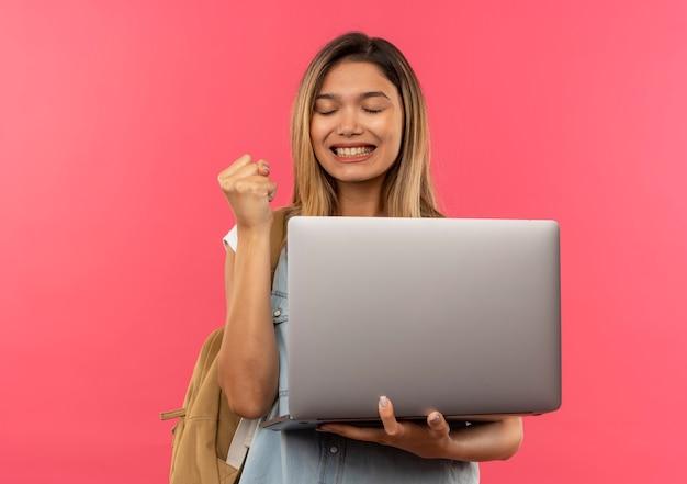 Счастливая молодая симпатичная студентка в задней сумке держит ноутбук и сжимает кулак с закрытыми глазами, изолированными на розовом с копией пространства