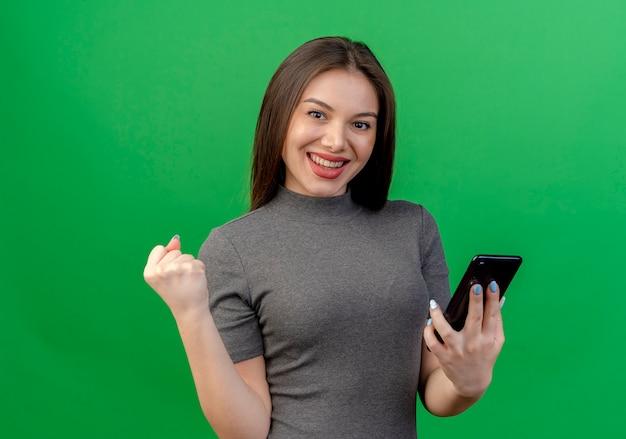 Felice giovane donna graziosa che tiene il telefono cellulare e il pugno di serraggio isolato su sfondo verde