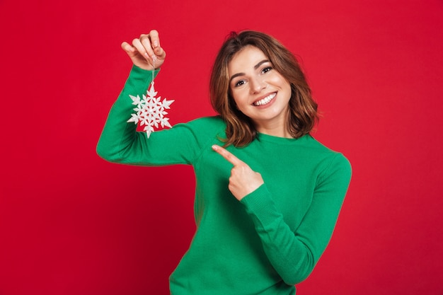 Happy young pretty woman holding snowflake pointing.