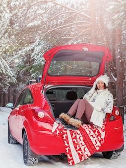 행복한 젊은 예쁜 여자가 겨울에 숲에서 열린 차 트렁크에 앉아 있다