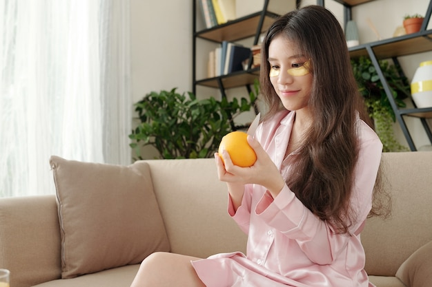 Happy young pretty woman peeling fresh orange for breakfast when sitting on sofa in pajamas after waking up