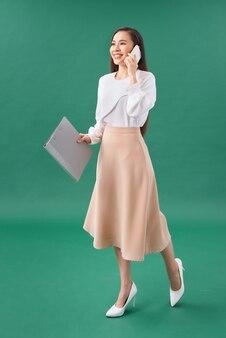 행복 한 젊은 예쁜 여자 휴대 전화로 얘기 하는 폴더를 들고 청록색 배경 위에 고립 된 포즈.