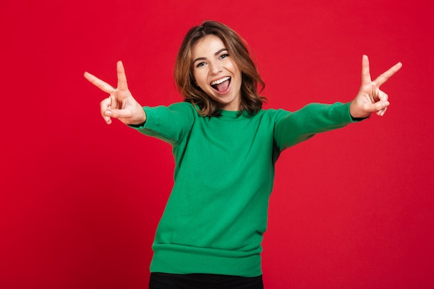 Happy young pretty woman showing peace gesture.