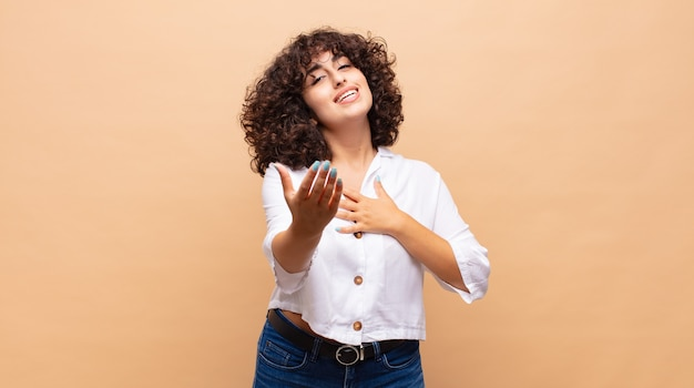 巻き毛の幸せな若いきれいな女性