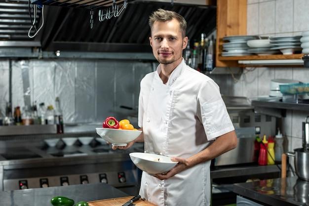 野菜サラダや他のコースのための新鮮なトウガラシと2つのセラミックボウルを保持している白い制服を着た幸せな若いプロのシェフ