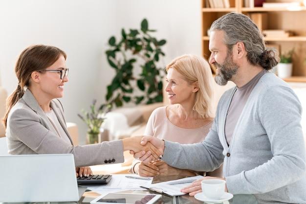 Счастливый молодой агент по недвижимости поздравляет своих зрелых клиентов с успешной сделкой после подписания всех документов