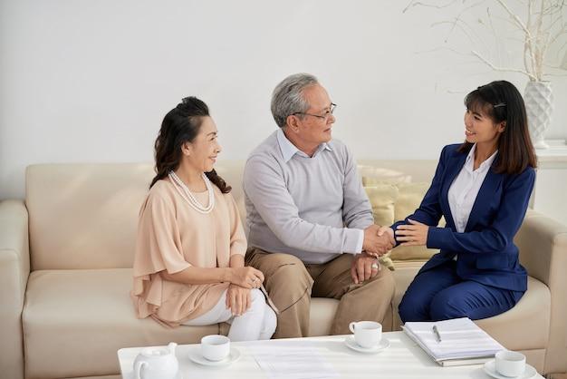 행복한 젊은 부동산 매니저는 성공적인 회의 후 노인들과 악수를 하고 있습니다.