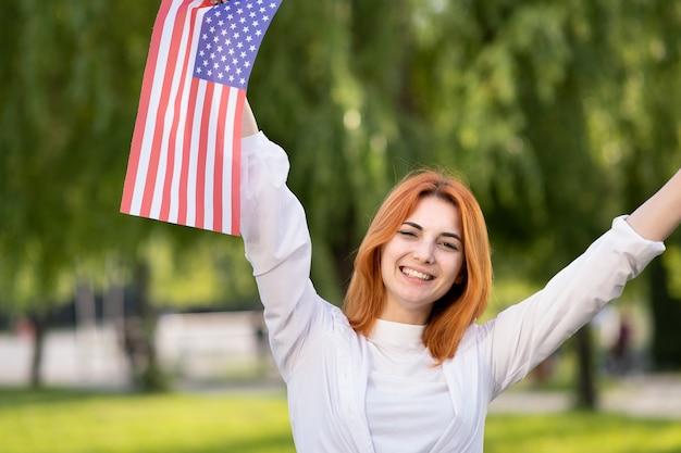 彼女の手で屋外で米国の国旗を保持している幸せな若い赤い髪の女性