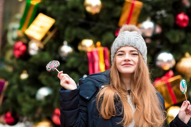 クリスマスのトウヒに対しておいしいキャラメルキャンディーを保持している灰色のニット帽の幸せな若い赤い髪の女性