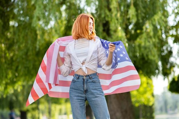 Счастливая молодая рыжая женщина позирует с национальным флагом сша на плечах