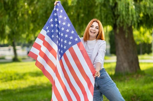 Счастливая молодая рыжеволосая женщина позирует с национальным флагом сша, стоя на открытом воздухе в летнем парке. позитивная девушка празднует день независимости соединенных штатов.