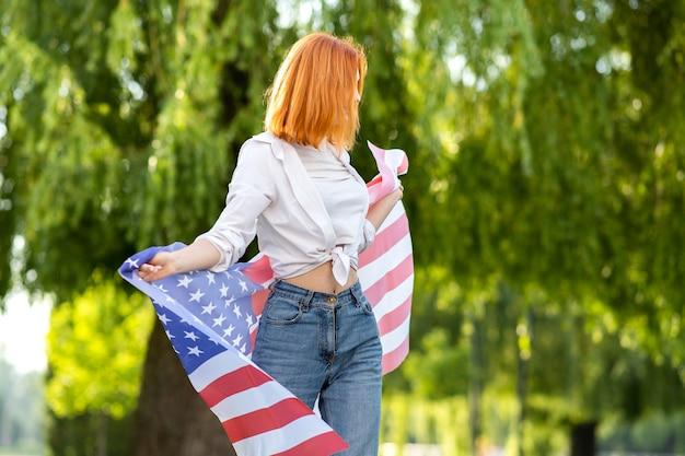 Счастливая молодая рыжая женщина позирует с национальным флагом сша, стоя на открытом воздухе