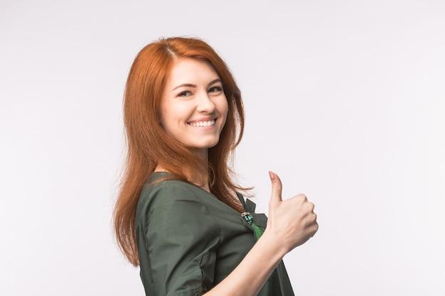 白い壁に親指を表示して幸せな若い赤毛の女性。