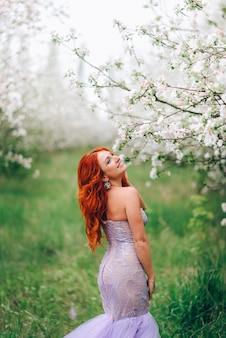 Счастливая молодая рыжеволосая женщина стоит в цветущем яблоневом саду, портрет