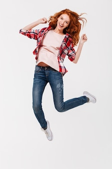 Happy young redhead lady jumping isolated