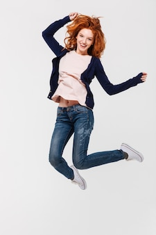 Happy young redhead lady jumping