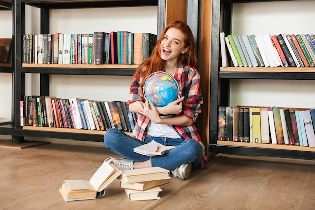 Happy young redhead pretty lady in library
