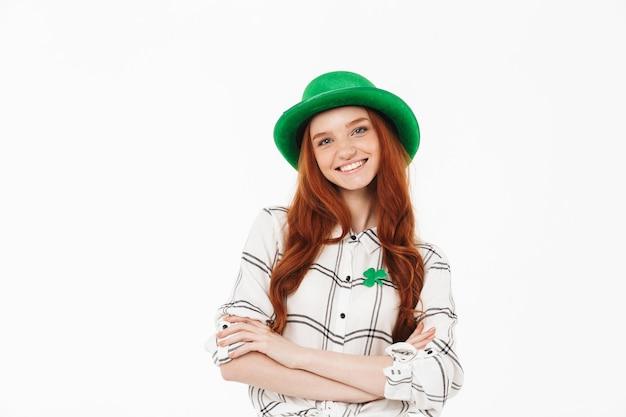 Счастливая молодая рыжеволосая девушка в зеленой шляпе празднует день святого патрика изолирована над белой стеной, скрестив руки на груди