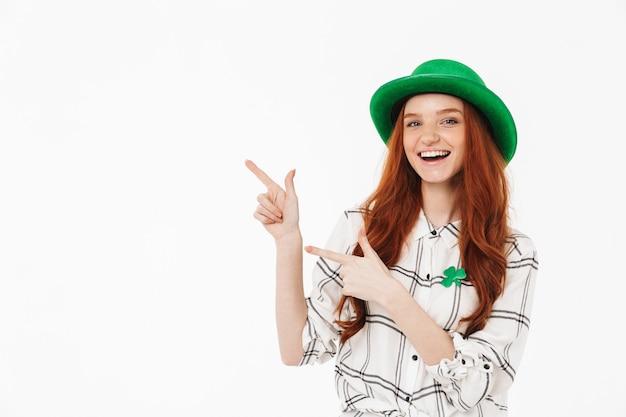Счастливая молодая рыжеволосая девушка в зеленой шляпе празднует день святого патрика изолирована над белой стеной, указывая пальцем