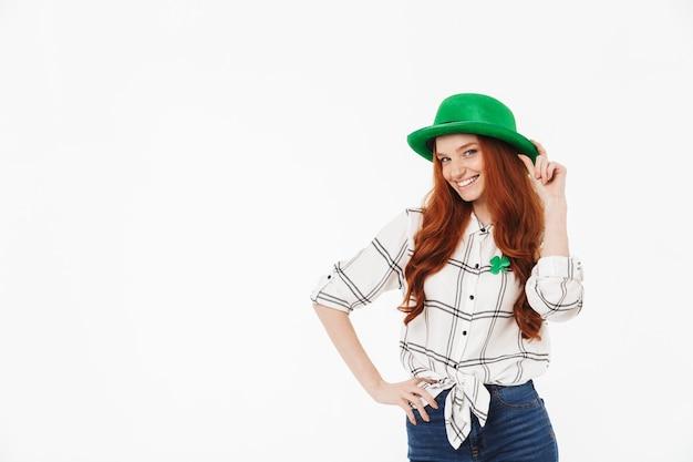 Счастливая молодая рыжеволосая девушка в зеленой шляпе, празднует день святого патрика, изолирована над белой стеной, позирует