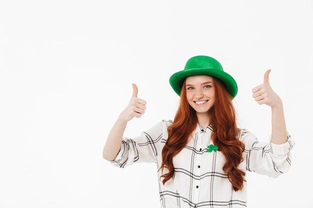 Счастливая молодая рыжеволосая девушка в зеленой шляпе празднует день святого патрика, изолированную над белой стеной, показывает палец вверх