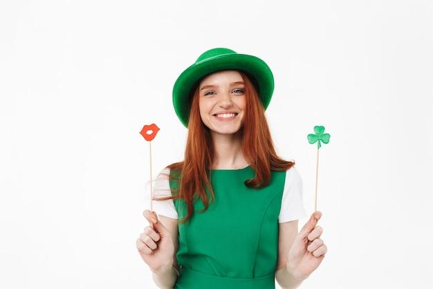 Счастливая молодая рыжеволосая девушка в зеленой шляпе празднует день святого патрика, изолированную над белой стеной