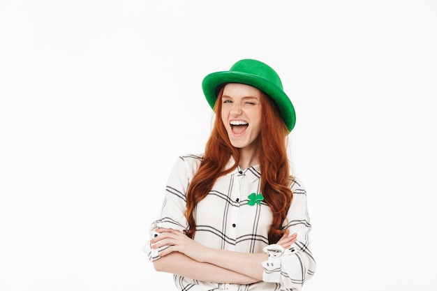 Happy young redheaded girl wearing green hat, celebrating st patricks's day isolated over white wall, arms folded