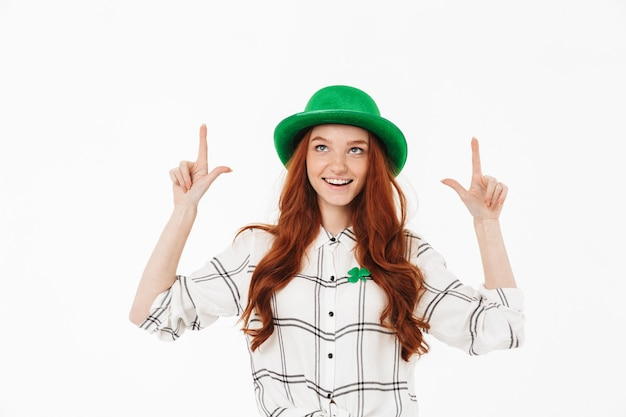 Happy young redheaded girl wearing green hat, celebrating st patricks's day isolated over white wall, pointing finger