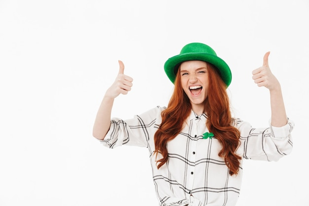 Happy young redheaded girl wearing green hat, celebrating st patricks's day isolated over white wall, thumbs up