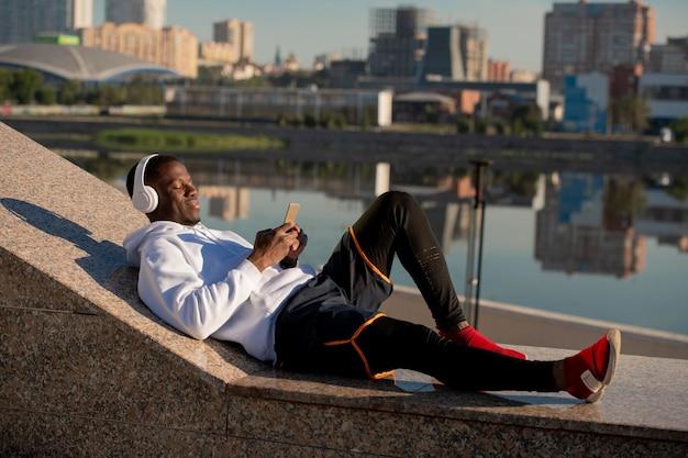 도시 환경에서 강변에 누워 헤드폰으로 음악을 듣고 아프리카 민족의 행복 젊은 편안한 스포츠맨