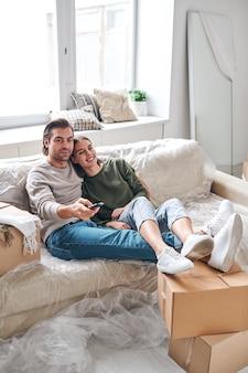 Счастливая молодая спокойная пара расслабляется на диване, сидя перед телевизором, положив ноги на упакованные коробки после переезда в новую квартиру