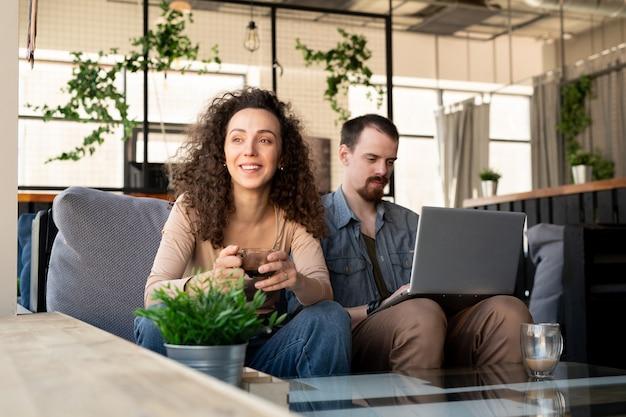 ソファに座って窓越しに見ているお茶やコーヒーと幸せな若い安らかな女性