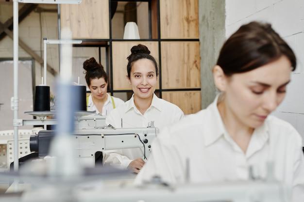 Счастливая молодая швея с зубастой улыбкой смотрит на вас среди своих коллег, шьет новую одежду на машине в мастерской