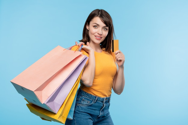 ショッピングに成功した後、黄色のクレジットカードを誇るいくつかの紙袋を持つ幸せな若い買い物中毒