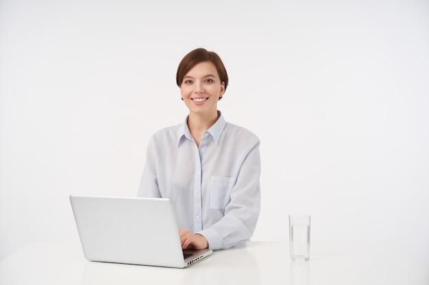 彼女のラップトップで作業し、白の上に座って、広く笑って、自然なメイクで幸せな若い短い髪のブルネットの女性