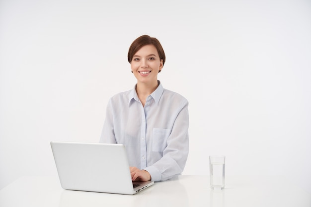Happy young short haired brunette woman with natural makeup working with her laptop and smiling widely, sitting on white