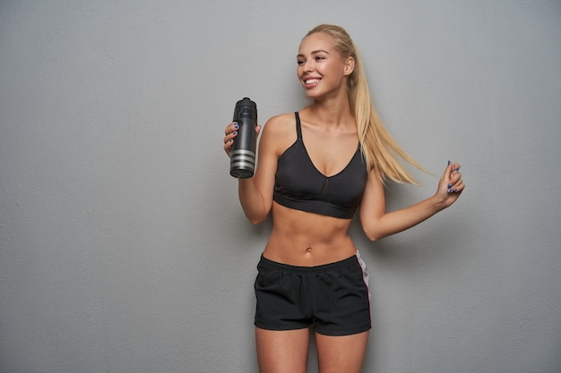 Happy young slim blonde female with ponytail hairstyle smiling widely while looking aside and pulling her hair, drinking water after hard workout, standing over light grey background
