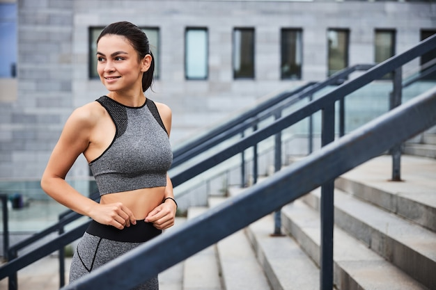 Happy young slim female is standing in outfit on stairs of urban building before training outdoors