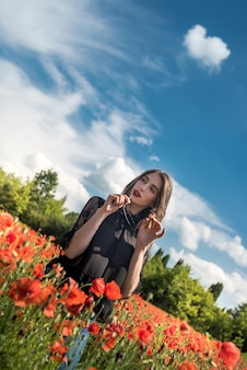 Happy young slim girl walk in red poppies field, spending time, summer